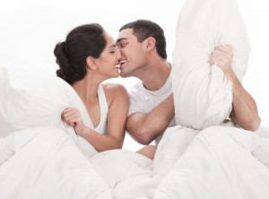 happy couple kissing in bed